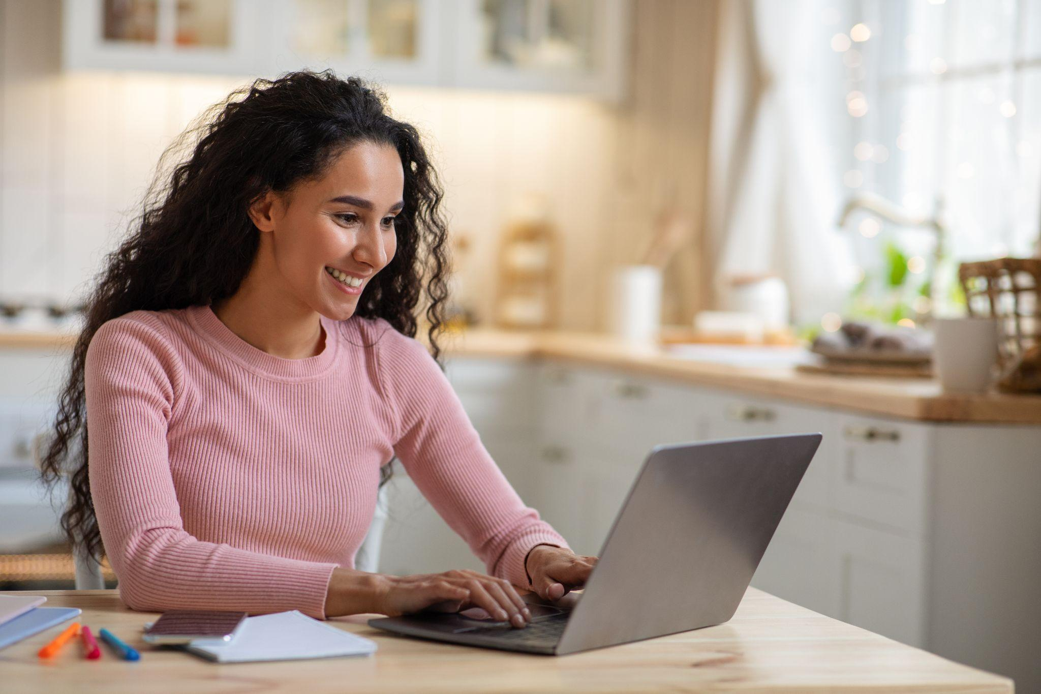 Women typing on a laptop at her kitchen table
