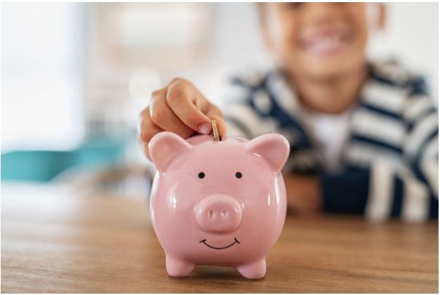 Child putting coin in piggybank